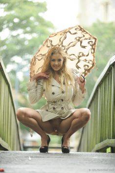 В плаще под зонтом
