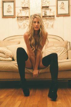 Длинноногая блондинка на диване в чулках
