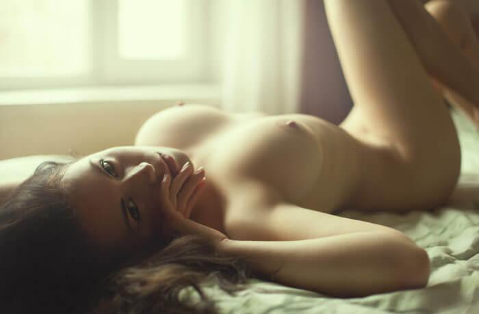 Позирует голышом на кровати