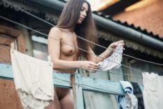 Голая девушка развешивает бельё