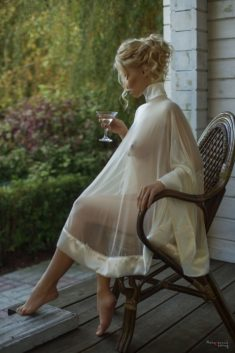 Блондинка в просвечивающем платье на веранде