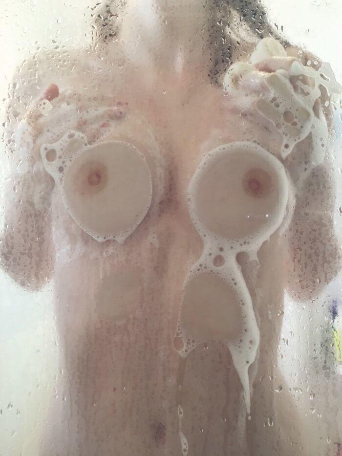 Прислонилась грудью к стеклу