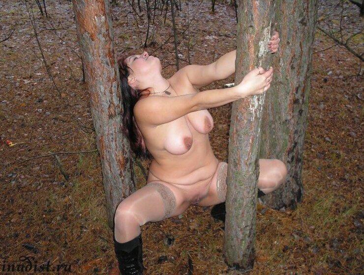 Голая в лесу у дерева