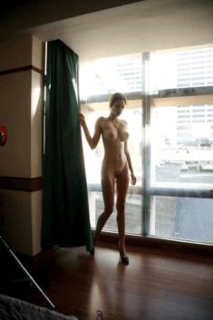 Голая худышка у окна